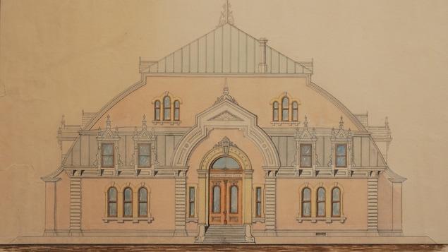 Un bâtiment au toit en forme d'arche se dresse, avec en façade de nombreuses fenêtres aux contours ouvragés. Un escalier élégant mène à une double porte vitrée en bois.