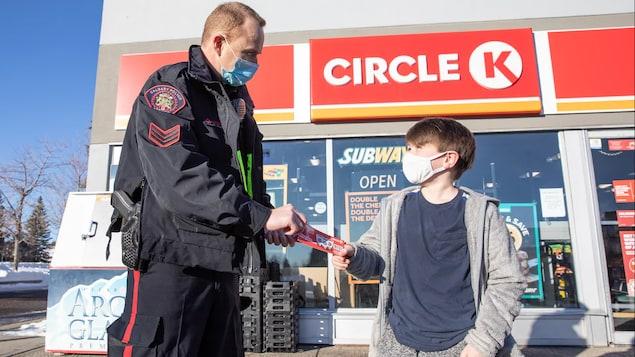 Un agent de police donne un billet à un petit garçon devant un dépanneur Circle K. Tous les deux portent un masque.