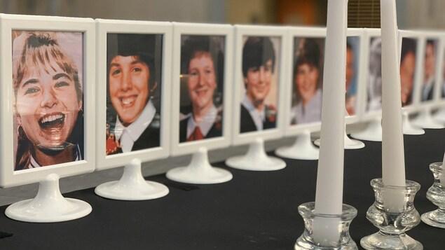 Les photos des 14 victimes de Polytechnique dans des cadres posés sur une table avec une rangée de chandelles blanches.