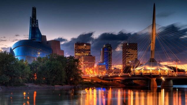 Photographie de l'esplanade Riel avec le Musée pour les droits de la personne et le centre-ville de Winnipeg.