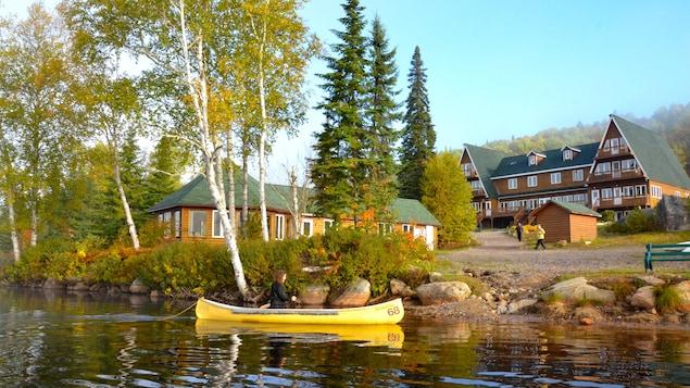 Une femme en canot sur un lac. Un grand chalet de bois et une montagne en arrière-plan.
