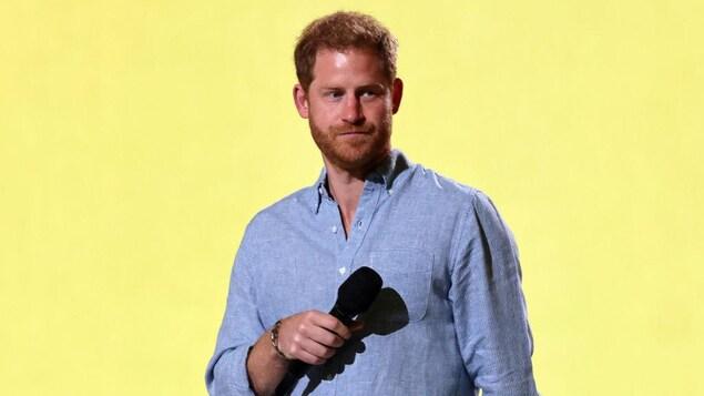 L'homme porte une chemise bleue et tient un micro dans la main droite.