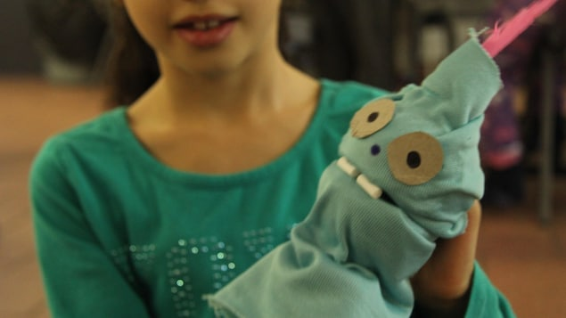 Une enfant tient une marionnette verte fabriquée à la main.