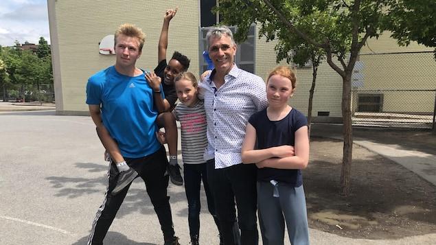 Quentin Tison et d'autres personnes à l'extérieur d'une école.
