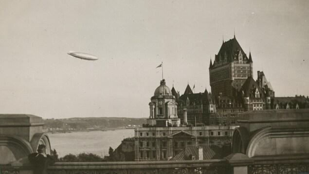 Un jeune prêtre observe le dirigeable en direction du château Frontenac dans le ciel de Québec. Il est accoudé à une balustrade ouvragée, sur le toit dégagé d'un grand édifice. On le voit de dos, mais il tient visiblement des longues vues.