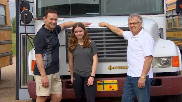Deux hommes et une jeune femme devant un autobus, souriant. Ils sont tous de la même famille.