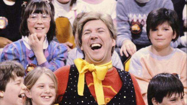 Rémy Girard, costumé et rieur, est assis parmi un groupe d'enfants,