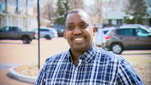 Renord Nsekera tout souriant devant la caméra, dehors, par une journée de printemps.