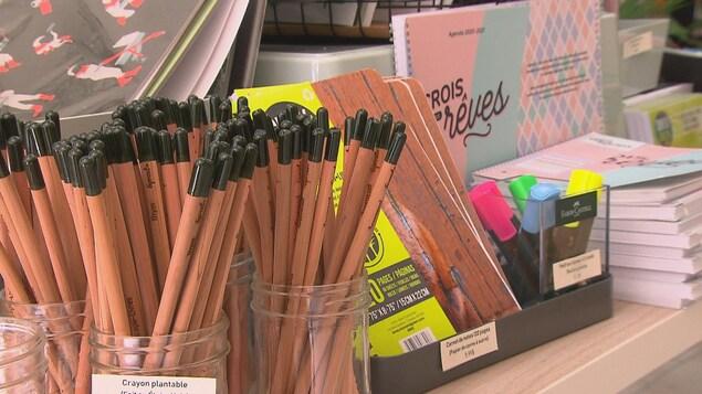 Des crayons et des cahiers fabriqués de matières recyclées dans un commerce.