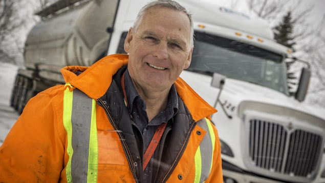 Richard Bilodeau devant un camion de transport.
