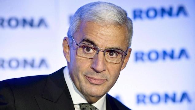 Un homme aux cheveux gris est photographié devant des panneaux sur lesquels on peut lire « Rona ».