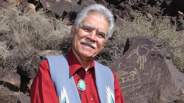 Rudolfo Anaya prend la pose près de pétroglyphes, au Nouveau-Mexique.