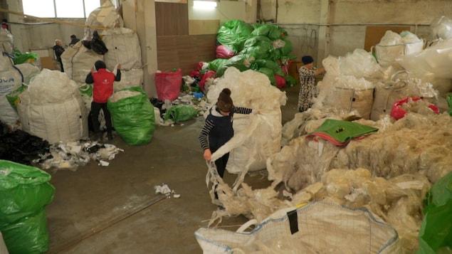 Trois personnes s'affairent à trier des déchets dans un entrepôt où s'empilent des sacs remplis de matières recyclables.