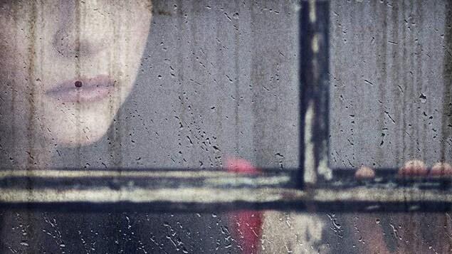 Visage tronqué d'une femme derrière une vitre sous la pluie