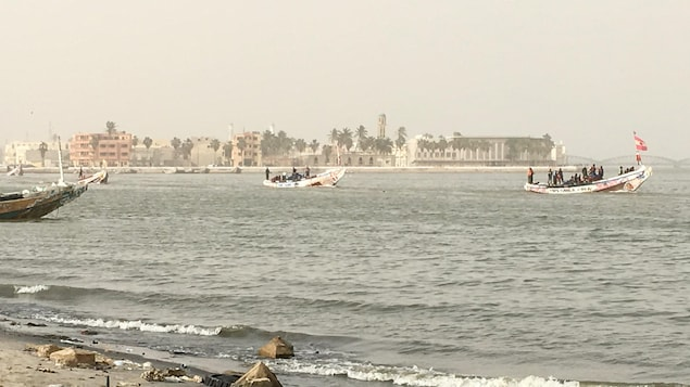 Des bateaux voguent, et en arrière-plan, des immeubles.