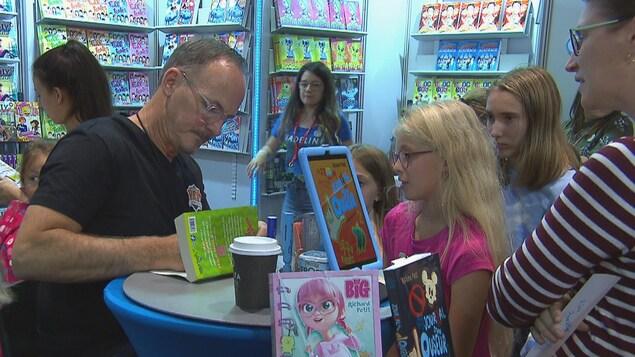 Un auteur signe un livre devant de jeunes lectrices.