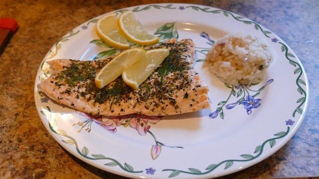 Une assiette avec des fleurs bleues et roses dans laquelle est déposé le saumon avec du riz et du citron.