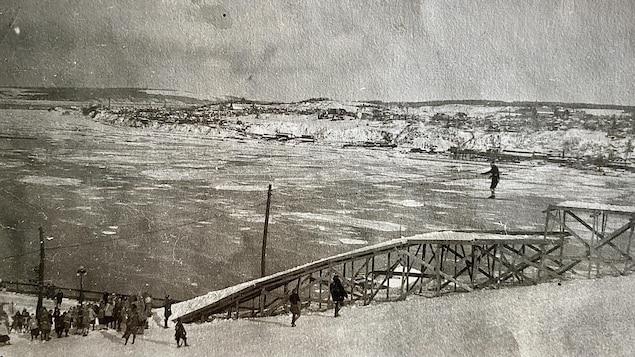 Une rampe de saut à ski dans les années 1920. On voit un skieur s'élancer. Il semble hésitant. La journée d'hiver est belle, derrière, on voit la glace sur le fleuve, la côte de Lévis, et une petite foule de spectateurs en bas de la rample.
