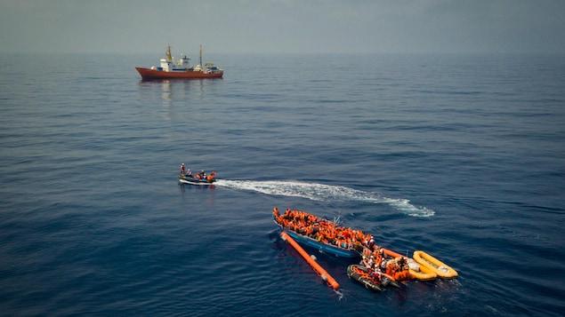Une opération de sauvetage en Méditerranée. En arrière-plan un grand navire de sauvetage. En avant-plan, des bateaux pneumatiques viennent en aide à une embarcation de migrants.