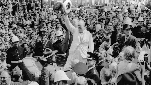 Churchill et Mackenzie King saluent triomphalement la foule compacte qui l'entoure, debout dans leur voiture décapotable. Même les responsables de la sécurité ne peuvent s'empêcher de sourire.