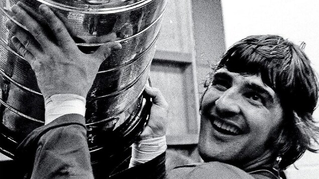 Photo en noir et blanc du joueur de hockey Serge Savard souriant, tenant à bout de bras la coupe Stanley.