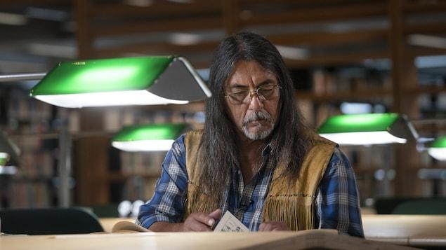 Serge Simon lit un vieux manuel scolaire à la Collection nationale, située à la Grande Bibliothèque à Montréal.