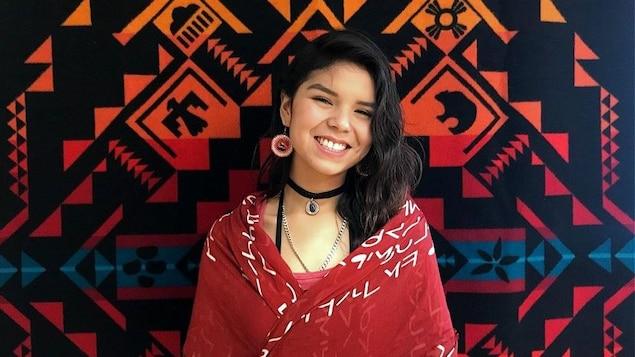 Shaunteya a des cheveux noirs de jais. Drapée dans un châle rouge, elle pose tout sourire devant une tapisserie autochtone. Elle porte aussi des boucles d'oreilles rouges au centre desquelles se trouve un cheval.
