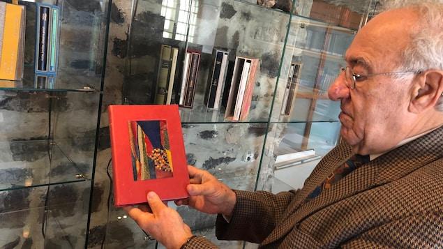 Philippe Sauvageau, président du SILQ, nous montre les oeuvres reliées qui ornent habituellement les bibliothèques de son bureau. Un homme vieillissant tient un livre rouge.