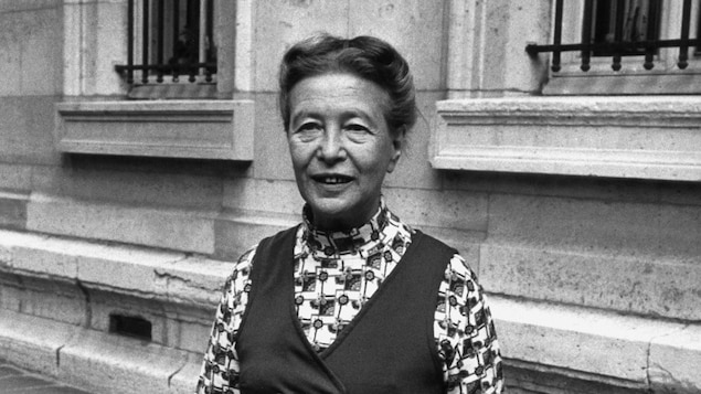 Simone de Beauvoir traverse une rue en souriant.