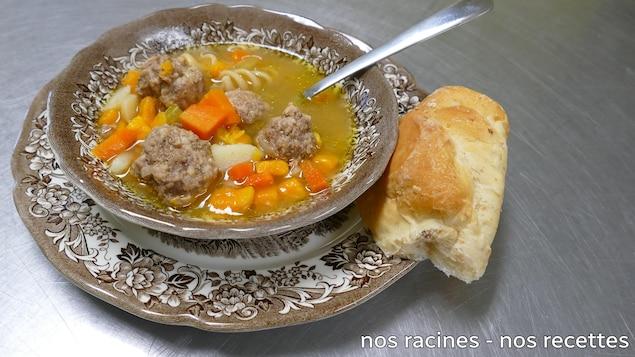 La soupe aux boulettes et légumes dans un plat de service brun avec du pain croûté et ne cuillère.