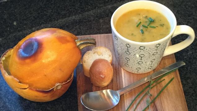 Sur une planche de bois, une tasse de soupe à la courge et juste à côté, la courge cuite coupée en deux, avec deux petits morceaux de pain et une cuillère