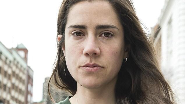 Portrait de l'auteure Stéfanie Clermont en chandail vert, cheveux châtains longs lâchés portés sur le côté gauche.