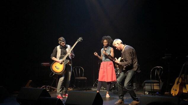 Le bassiste Jory Fernstrom, la chanteuse Ghislaine Doté et le guitariste et compositeur Jonathan Eltis sur la scène du théâtre Waterfront à vancouver.