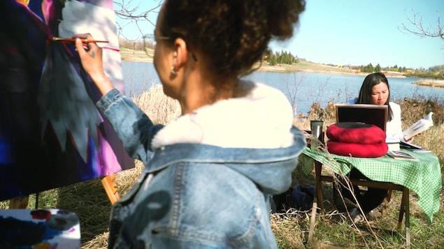 Sur le bord d'un lac à Regina en Saskatchewan, l'artiste visuelle Diana Ntibandetse peint pendant que la poète Thuy Nguyen écrit.