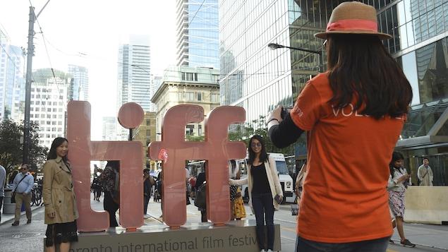 Une bénévole prend une photo de deux jeunes femmes devant un logo géant du TIFF.