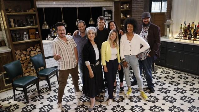 Des comédiens de Watatatow et les collaborateurs de Tournée générale sont debout dans un restaurant et sourient à la caméra.