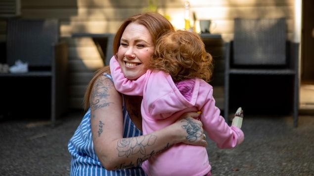Une mère fait un calin à son enfant.