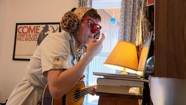 Une clown joue du ukulele devant un ordinateur portable.