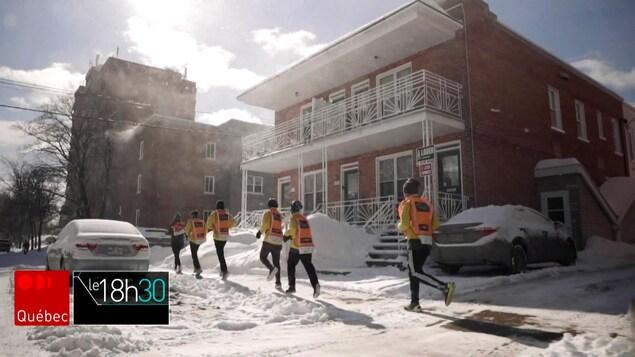 Des jeunes courent sur un trottoir, l'hiver.