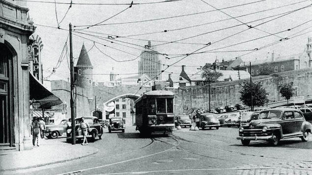 Le tramway sur la Place d'Youvlle, au coeur de l'action. On voit un impressionnant réseau de filage au-dessus des rails, couvrant le ciel sur presque toute la place