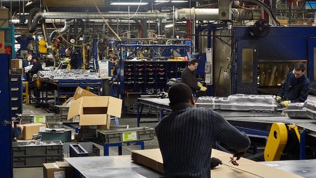 Des employés, certains de dos, certains de profil, qui travaillent à l'usine Spectra Premium de Boucherville.