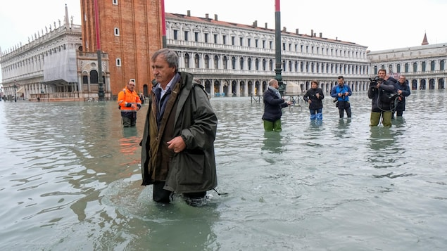 Luigi Brugnaro marche dans quelques dizaines de centimètres d'eau, sous les regards de journalistes.
