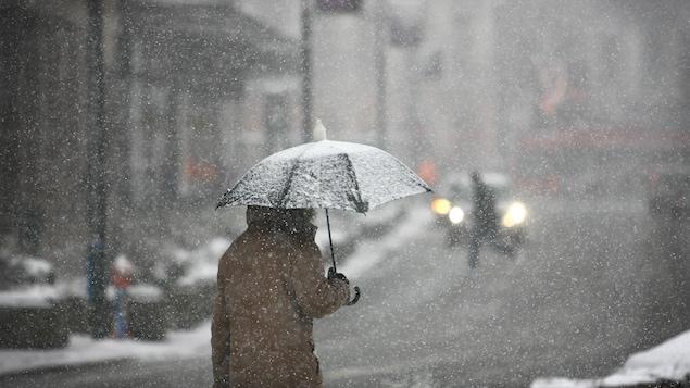 Un homme marche avec un parapluie dans une rue enneigée.
