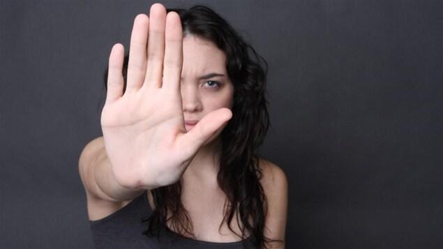 Une femme dresse sa main devant son visage.