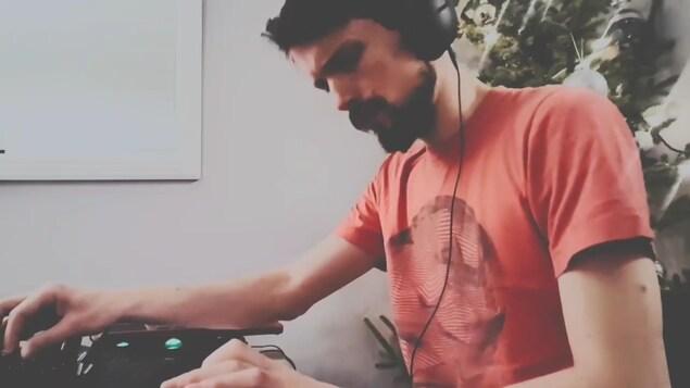Gabriel Fields, avec un casque sur les oreilles et une console audio au bout des doigts.