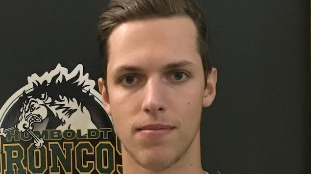 Gros plan du visage de Xavier Labelle devant le logo des Broncos de Humboldt.