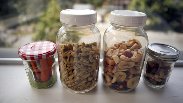 4 bocaux en verre remplis d'aliments : noix, biscuits, carottes