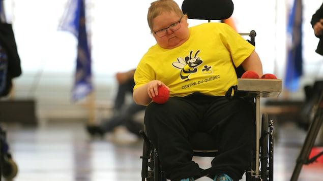 Un jeune homme en fauteuil roulant s'apprête à lancer une balle rouge.