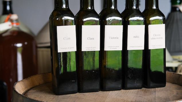 Des bouteilles de vinaigres artisanaux sur une barrique de bois.