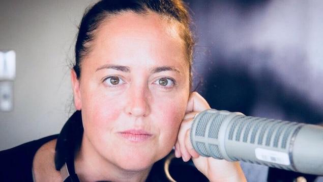 L'animatrice pose derrière le micro d'un studio de Radio-Canada.